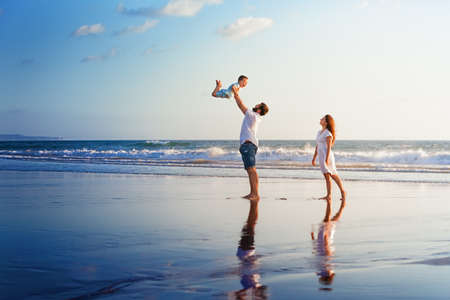 Foto de Happy family - father, mother, baby son walk with fun along edge of sunset sea surf on black sand beach. Active parents and people outdoor activity on summer vacations with children on Bali island - Imagen libre de derechos