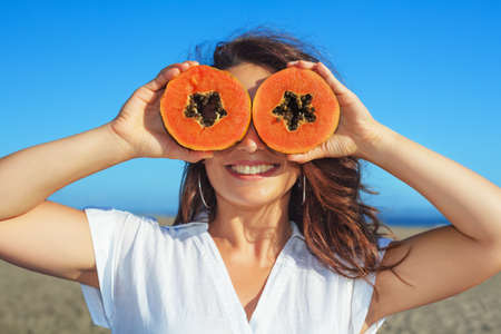Photo for Funny photo of positive adult woman with smiling face holding in hands ripe fruit - orange papaya slices. Healthful food, low calories breakfast on sea beach Healthy lifestyle on summer family holiday - Royalty Free Image