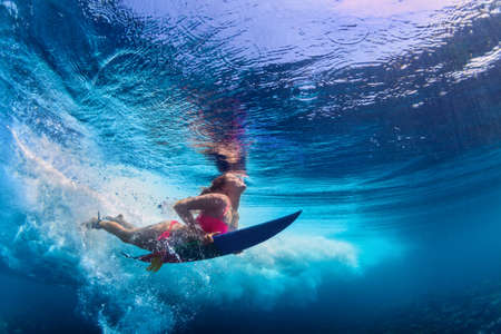 Foto de Young active girl wearing bikini in action - surfer with surf board dive underwater under big ocean wave. Family lifestyle, people water sport adventure camp and beach extreme swim on summer vacation. - Imagen libre de derechos