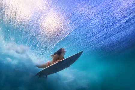Foto de Sportive girl in bikini in action. Surfer with surf board dive underwater under breaking ocean wave. Healthy lifestyle. Water sport, swim and extreme surfing in adventure camp on summer beach vacation - Imagen libre de derechos
