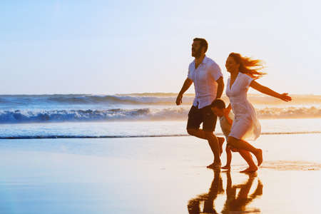 Foto de Happy family - father, mother, baby son hold hands and run together with fun along sunset sea surf on black sand beach. Travel, active lifestyle, parents with children on tropical summer vacations. - Imagen libre de derechos