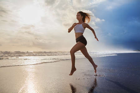 Photo pour Active sporty woman run along ocean surf by water pool to keep fit and health. Sunset black sand beach background with sun. Woman fitness, morning workout and sport activity on summer family holiday. - image libre de droit