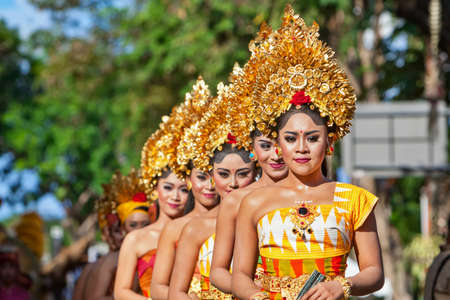 Photo for DENPASAR, BALI ISLAND, INDONESIA - JUNE 11, 2016: Group of Balinese people. Beautiful dancer women in traditional costumes dance on street parade at art and culture festival. - Royalty Free Image