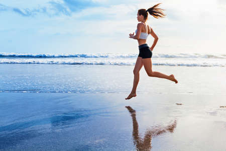 Photo pour Active sporty woman run along ocean surf by water pool to keep fit and health. Sunset black sand beach background with sun. Woman fitness, jogging workout and sport activity on summer family holiday. - image libre de droit