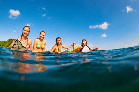 Photo pour Happy girls in bikini have fun - group of surfers sit on surf boards, young women wait for big ocean wave. People in water sport adventure camp, beach extreme activity on summer beach family vacation - image libre de droit