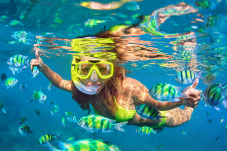 Photo for Happy family - girl in snorkeling mask dive underwater with fishes school in coral reef sea pool. Travel lifestyle, water sport outdoor adventure, swimming lessons on summer beach holidays with child. - Royalty Free Image