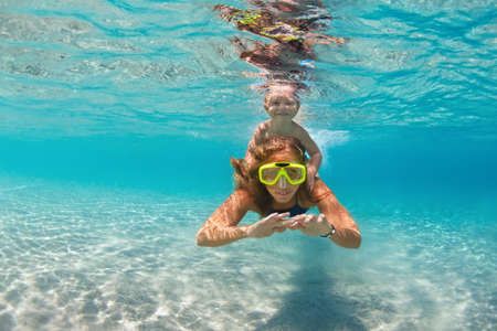 Photo for Happy active family - mother, baby son snorkel and dive together underwater in sea pool. Healthy people lifestyle, water sport outdoor adventure, swimming lesson on summer beach vacation with child - Royalty Free Image