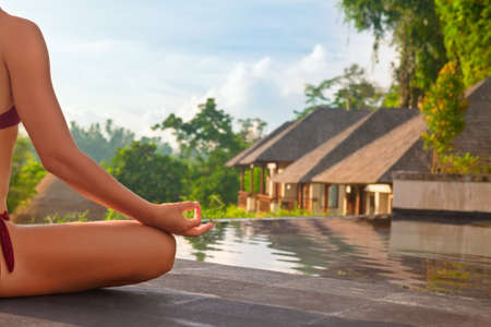 Photo pour Good morning with yoga meditating on sunrise background. Active woman in bikini practicing on villa poolside to keep fit and health. Woman fitness training, sport activity on summer family holiday. - image libre de droit