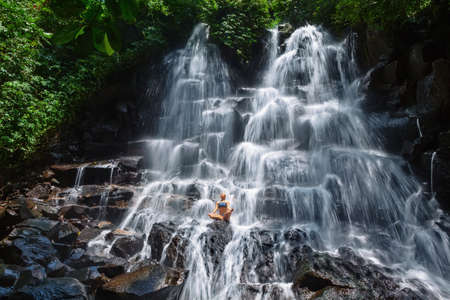 Photo for Travel in Bali jungle. Beautiful young woman sit in zen-like yoga pose under falling spring water, enjoy tropic cascade waterfall. Nature day trip, walking adventure, fun on family summer vacation - Royalty Free Image