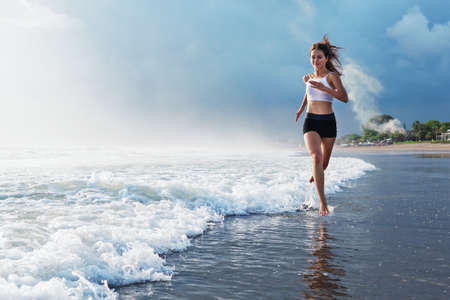 Foto de Active sporty woman run along ocean surf by water pool to keep fit and health. Sunset black sand beach background with sun. Woman fitness, jogging training and sport activity on summer family holiday. - Imagen libre de derechos