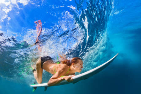 Foto de Active girl in bikini in action. Surfer woman with surf board dive underwater under breaking big wave. Healthy lifestyle. Water sport, extreme surfing in adventure camp on family summer beach vacation - Imagen libre de derechos
