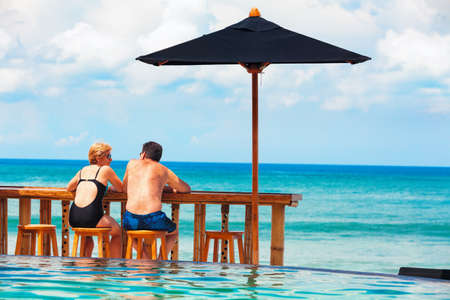 Photo pour Successful retirement recreation, summer vacation concept. Retired mature couple enjoying beautiful sunny day in swimming pool at beach club. Happy senior woman and man sitting at poolside beach bar. - image libre de droit