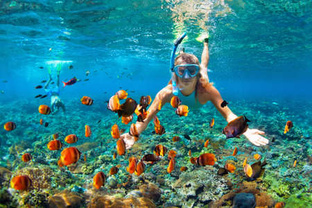 Photo pour Happy family - couple in snorkeling masks dive deep underwater with tropical fishes in coral reef sea pool. Travel lifestyle, outdoor water sport adventure, swimming lessons on summer beach holiday - image libre de droit