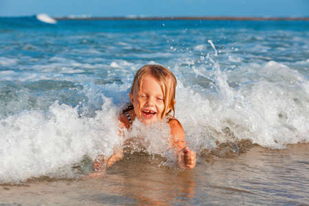 Photo pour Happy family lifestyle. Baby girl splashing and jumping with fun in breaking waves. Summer travel, water sport outdoor activities, swimming lessons on tropical beach holiday with kids. - image libre de droit