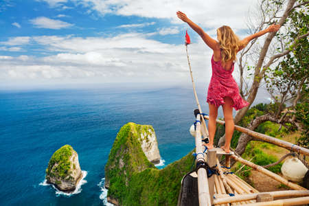 Photo pour Family vacation lifestyle. Happy woman with raised in air hand stand at viewpoint. Look at beautiful beach under high cliff. Travel destination in Bali. Popular place to visit on Nusa Penida island - image libre de droit