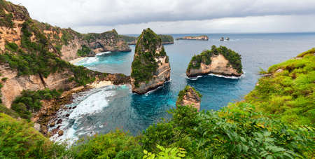 Foto de Sea coast view with little house standing on the high cliff bring above sea and little rocky islets. Atun beach, Nusa Penida island. Popular travel destination on Bali holidays. Indonesian background. - Imagen libre de derechos
