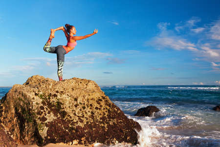 Foto de Meditation on sunset sky background. Young active woman stand in yoga pose on beach rock to keep fit and health. Healthy lifestyle, outdoor fitness, sport activity on summer family holiday. - Imagen libre de derechos