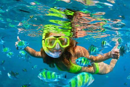 Photo pour Happy family - girl in snorkeling mask dive with tropical fishes in coral reef sea pool. Travel lifestyle, water sports outdoor adventure, underwater swimming on summer beach holiday with kids. - image libre de droit