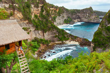 Foto de Happy family travel lifestyle. Mother with child sit on steps of traditional house on tree, look at Atun beach, Nusa Penida island. Popular travel destination on Bali holidays. Indonesian background. - Imagen libre de derechos