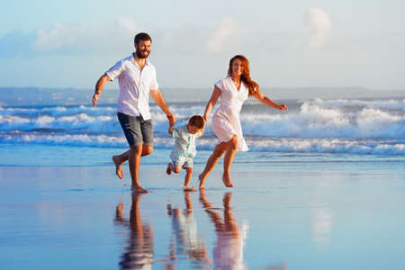 Foto de Happy family - father, mother, baby son have fun together, child run with splashes by water pool along sunset sea surf on black sand beach. Travel lifestyle, parents with kids on summer vacation. - Imagen libre de derechos