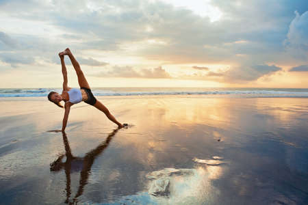 Foto per Meditation on sunset sky background. Young active woman in yoga pose on sea beach, stretching to keep fit and health. Healthy lifestyle, outdoor fitness, sports activity on summer family holiday. - Immagine Royalty Free