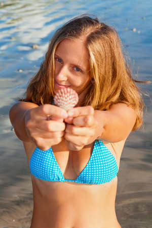 Photo pour Happy family lifestyle. Young smiling woman in bikini hold in hands sea shell. Summer travel, leisure and recreational activities on tropical beach holiday with kids. - image libre de droit