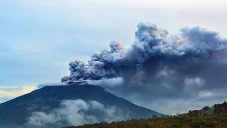Photo pour Mount Agung erupting plume. During volcano eruption thousands of people was evacuated from dangerous zone. Airline flights to Bali were canceled, Denpasar airport closed because of volcanic ash clouds - image libre de droit