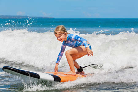Photo pour Happy baby girl - young surfer ride on surfboard with fun on sea waves. Active family lifestyle, kids outdoor water sport lessons and swimming activity in surf camp. Summer vacation with child. - image libre de droit