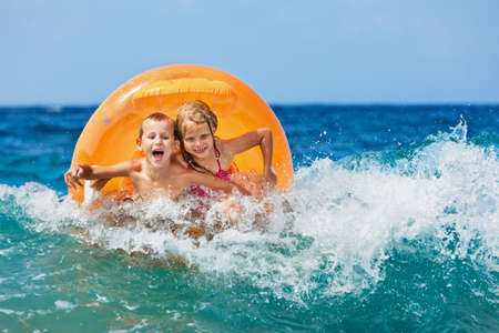 Photo for Happy kids have fun in sea surf on beach. Joyful couple of children on inflatable ring ride on breaking wave. Travel lifestyle, swimming activities in family summer camp. Vacations on tropical island - Royalty Free Image