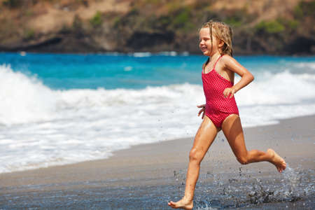 Foto de Happy barefoot child have fun on beach walk. Girl run along sea surf by water pool and jump with splashes. Family travel lifestyle, swimming activities. Summer vacation with kids on tropical island - Imagen libre de derechos
