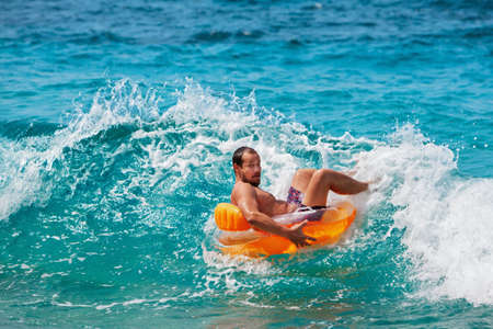 Foto de Excited bearded hipster in inflatable ring have fun in beach surf. Funny man riding on tubing in breaking sea waves. Family travel lifestyle, swimming activities. Summer vacation on tropical island. - Imagen libre de derechos