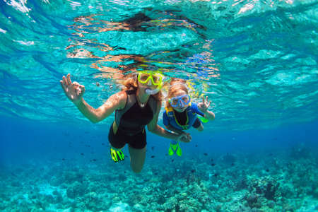 Photo pour Happy family - mother, kid in snorkeling mask dive underwater with tropical fishes in coral reef sea pool. Show by hands divers sign OK. Travel lifestyle, beach adventure on summer holiday with child. - image libre de droit