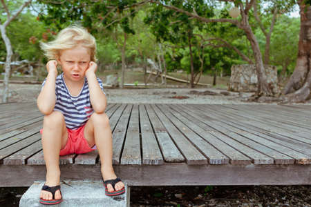 Photo for Funny portrait of caucasian kid looking annoyed and unhappy. Upset and angry child concept for family relations, social problems issues and juvenile psychology. Outdoor background with copy space. - Royalty Free Image