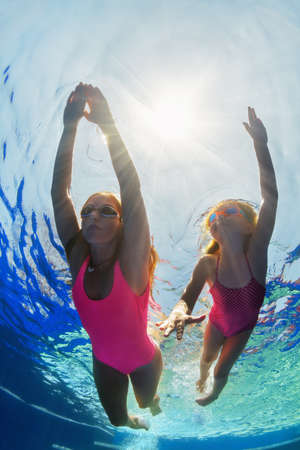 Photo pour Happy family - young mother, girl learn to swim and dive underwater. Jump with fun in swimming pool. Healthy lifestyle, active parents, people water sports activities on summer holidays with kids. - image libre de droit