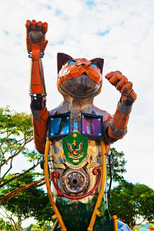 Foto de Kuching, Malaysia - March 11, 2019: Funny metal cat statue with Kuching city coat of arms at waterfront of Sarawak river. Cat is a symbol of Kuching city - popular travel destination in Borneo island - Imagen libre de derechos