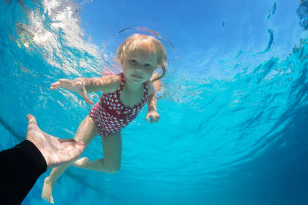 Photo for Happy family in swimming pool. Child jump deep down in pool with fun - dive underwater to reach extended hand. Healthy lifestyle, people water sport activity, swimming lessons on holidays with kids - Royalty Free Image