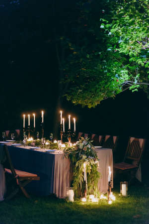 Photo pour Wedding. Banquet. The chairs and table for guests, decorated with candles, served with cutlery and crockery and covered with a tablecloth. The table stands on a green lawn in the backyard banquet area - image libre de droit