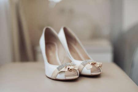 Foto de Bride wedding shoes with high heels and silver brilliant earrings on sheep's clothing - Imagen libre de derechos