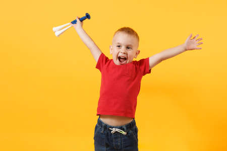 Photo pour Little cute kid baby boy 3-4 years old, football fan in red t-shirt holding in hand pipe, blowing isolated on yellow background. Kids sport family leisure lifestyle concept. Copy space advertisement - image libre de droit