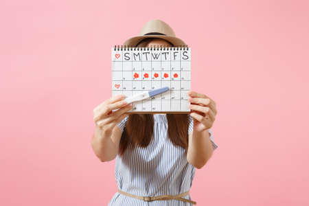Foto de Excited happy woman in blue dress, hat hold in hand pregnancy test, periods calendar for checking menstruation days isolated on pink background. Medical, healthcare, gynecological concept. Copy space - Imagen libre de derechos