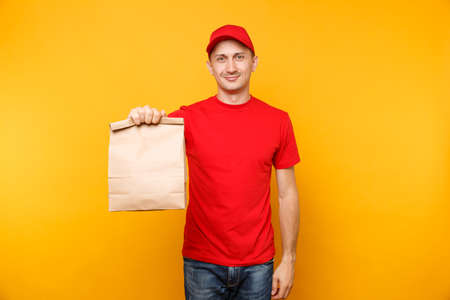 Photo pour Man in red cap, t-shirt giving fast food order isolated on yellow background. Male employee courier hold empty paper packet with food. - image libre de droit