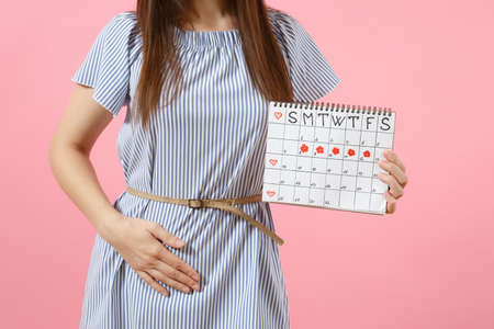 Photo for Portrait sad illness woman in blue dress holding periods calendar for checking menstruation days put hand on abdomen isolated on pink background. - Royalty Free Image