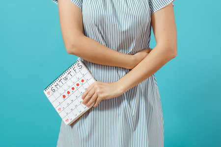 Foto de Cropped shot sickness woman in blue dress holding periods calendar for checking menstruation days put hand on tummy isolated on blue background. - Imagen libre de derechos