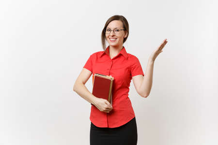 Foto de Portrait of young teacher woman in red shirt, skirt and glasses holding books, pointing hand aside on copy space isolated on white background. Education or teaching in high school university concept - Imagen libre de derechos