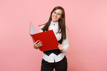 Foto de Young beautiful successful brunette business woman in glasses holding red folder for papers document isolated on pink background. Lady boss. Achievement career wealth. Copy space for advertisement - Imagen libre de derechos