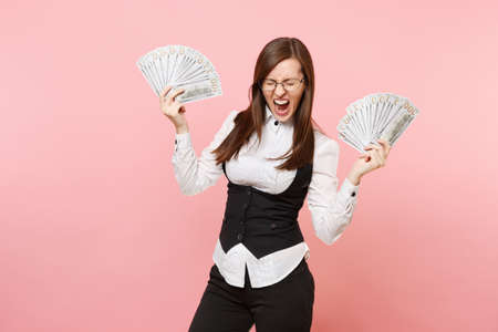 Foto de Young crazy business woman in glasses screaming hold bundle lots of dollars, cash money spreading hands isolated on pink background. Lady boss. Achievement career wealth. Copy space for advertisement - Imagen libre de derechos