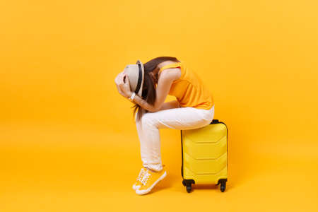 Foto de Upset tourist woman in summer casual clothes sit on suitcase put hands on head isolated on yellow orange background. Female traveling abroad to travel on weekends getaway. Air flight journey concept - Imagen libre de derechos