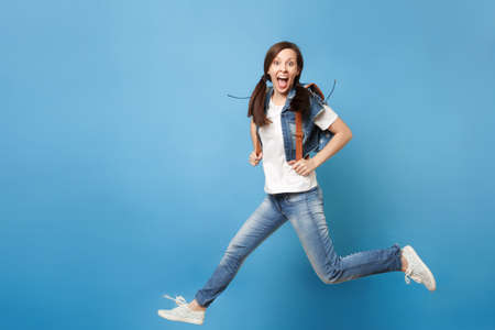 Foto de Full length portrait of young excited cheerful woman student with opened mouth with backpack jumping spreading legs isolated on blue background. Education in university. Copy space for advertisement - Imagen libre de derechos
