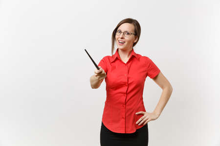 Foto de Portrait of young business teacher woman in red shirt skirt glasses holding wooden classroom pointer on copy space isolated on white background. Education teaching in high school university concept - Imagen libre de derechos