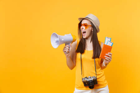 Photo pour Expressive tourist woman in summer casual clothes hat holding megaphone passport tickets isolated on yellow orange background. Female traveling abroad to travel weekends getaway. Air flight concept - image libre de droit